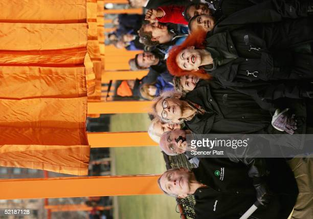 Artists Christo and JeanneClaude watches New York City Mayor Michael R Bloomberg unfurl of the one of the in the The Gates Central Park New York...