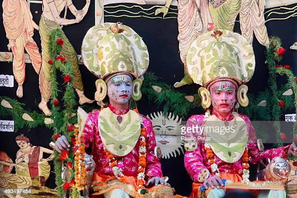Artists dressed as Hindu deities Laxman and Rama sit in a tableau during the Dussehra festival procession