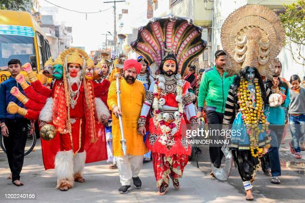 Artists dressed as Hindu deities Shiva Mata Kali and Hanuman walk as they take part in a religious procession on the occasion of 'Maha Shivaratri'...