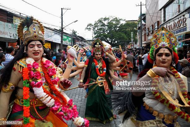 Artists dressed as Hindu goddesses perform on a street as they participate in 'Atachamayam' procession to herald the beginning of the tenday harvest...