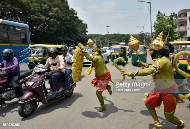 Artists dressed like the characters of Ramayana performing amid traffic during a road show on the occasion of 9th day of Navratri at a Hanuman Temple...