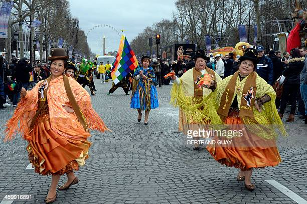 Artists dressed with Andean suits dance during the parade organized by French circuses on January 1, 2014 on the Champs-Elysees in Paris to celebrate...