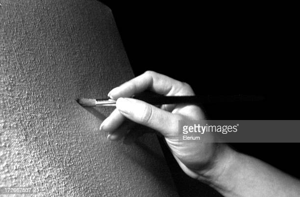 Artist's Hand Painting a Blank Canvas