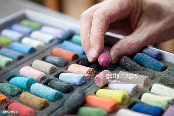 artist's hand reaching for a pink pastel crayon - chalk art equipment stock pictures, royalty-free photos & images