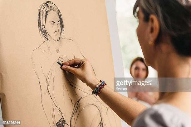 Artists in atelier charcoal drawing semi nude model