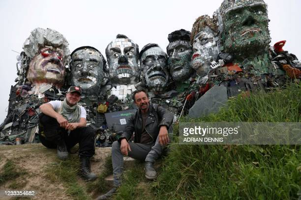 Artists Joe Rush and Alex Wreckage pose in front of a giant Mount Rushmore-style sculpture of the G7 leaders heads, made entirely of discarded...