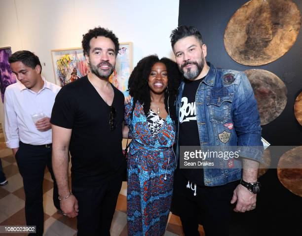 Artists Jules Arthur and Tim Okamura pose with a guest at the 2018 PRIZM Art Fair as part of Art Basel Miami Beach on December 9 2018 in Miami Florida