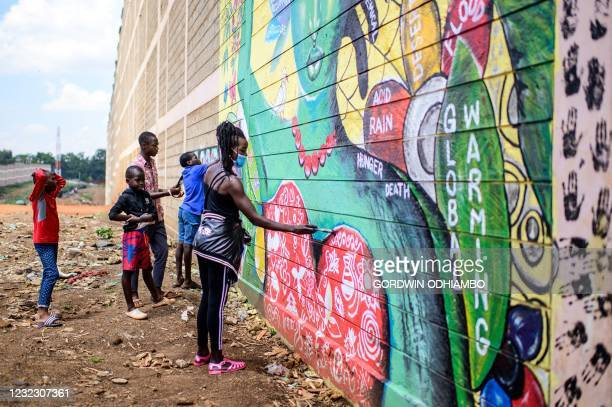 Artists of the local art project, Art 360, paint to complete the mural raising awareness on mental health and global climate changes in Kibera slum...