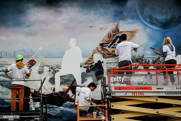 Artists paint a mural of characters from Sony Corp PlayStation video games before the start of the E3 Electronic Entertainment Expo in Los Angeles...