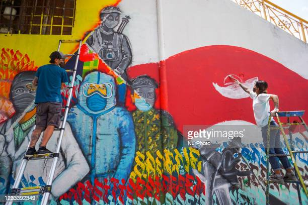 Artists paint a wall to show respect and gratitude to the frontline workers and to raise awarenessabout COVID-19 in Kathmandu, Nepal on June 11,...