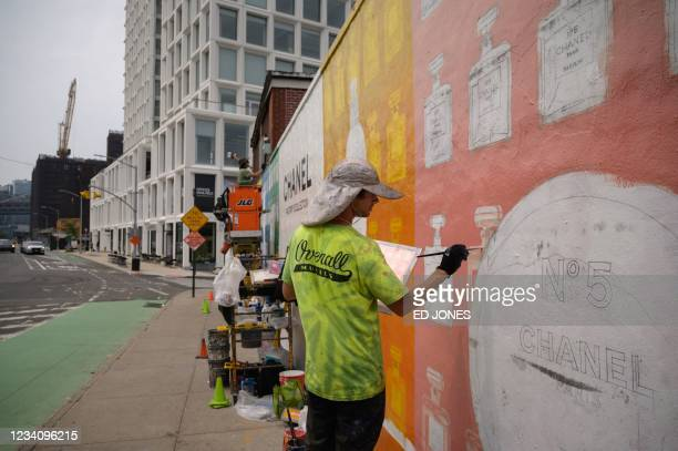 Artists paint an advertisement for fashion brand Chanel on a wall along a street in the gentrified Williamsburg neighborhood of Brooklyn, New York on...