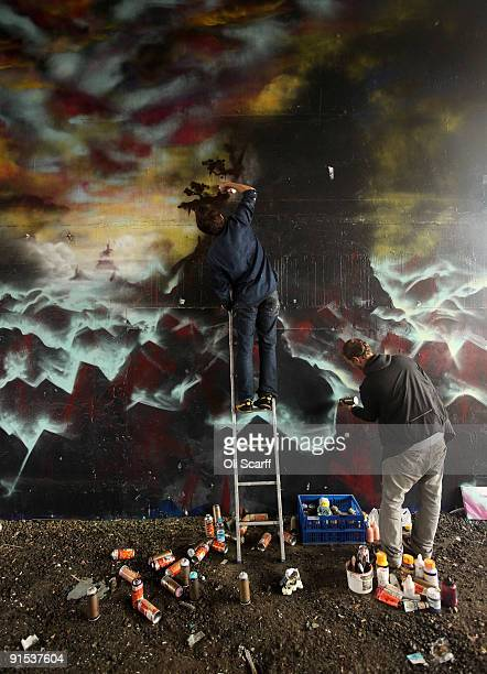 Artists put the finishing touches to the 'One Foot in the Grove' exhibition of street art by 'Mutate Britain' under the Westway flyover on October 6...