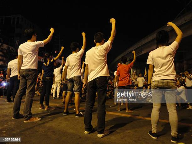 Artists raise their fists as they perform a presentation to the tune of a song honoring revolutionaries that were killed or have passed away near...