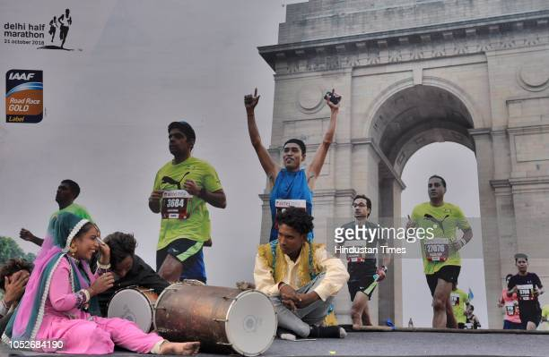 Artists share a light moment with each other infront of a hoarding during the Airtel Delhi Half Marathon at Rajpath on October 21 2018 in New Delhi...
