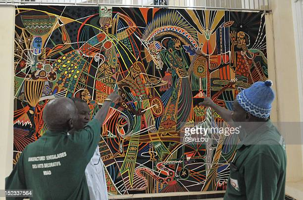 Artists stand in front of a handwoven tapestry which will decorate the headquarters of the United Nations in New York on September 4 at the tapestry...
