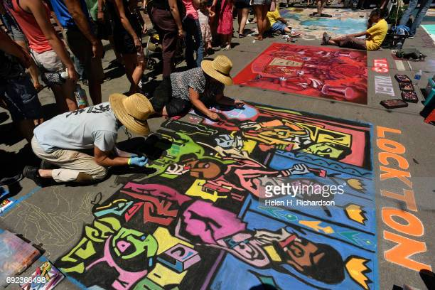 Artists Stanley Turner and Amy Cheslin work on their piece entitled The Country Wine Tasters inspired by the work of artist Michael Keyes during the...