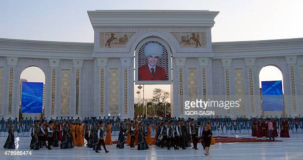 Artists take part in the opening ceremony of a new park, with a huge marble arch and a portrait of Turkmen President Gurbanguly Berdymukhamedov, in...