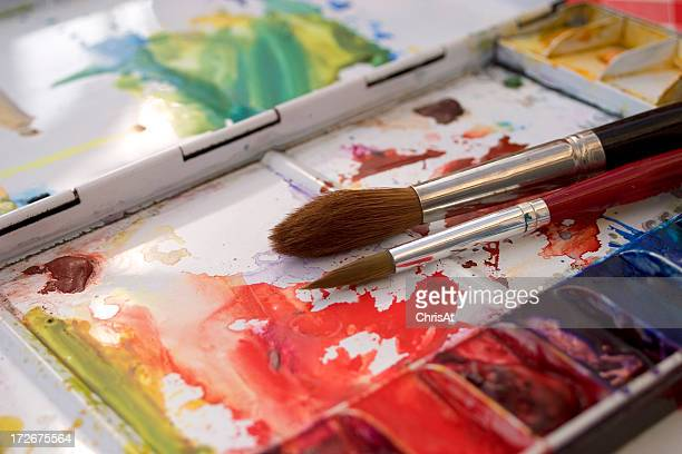 Artists watercolour paint palette and brushes in use close up