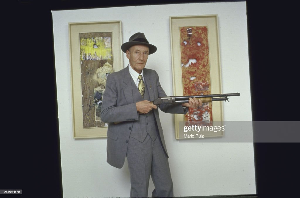 Artist/writer William S. Burroughs with shotgun standing in front of his shotgun paintings at an art gallery.