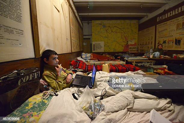 Artium 10yearsold sits in a bed with his laptop as he and others wait for the end of the shelling in Donetsk's Petrovski district in the eastern...