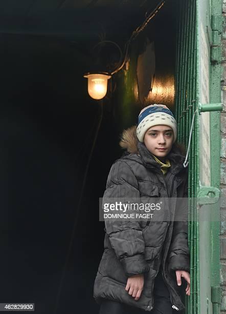 Artium10yearsold stands at the entrance of a bomb shelter in Donetsk's Kiyevski district in the eastern Ukraine on February 5 2015 Donetsk's Children...