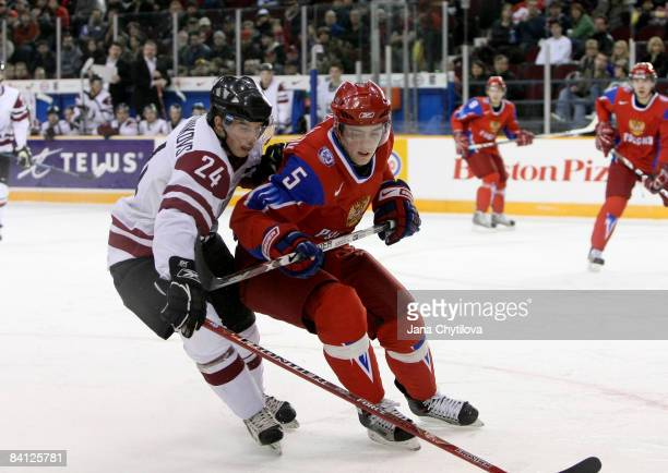 Artjoms Ogorodnikovs of Latvia battles for the loose puck with Maxim Goncharov in Ottawa, Ontario, Canada.