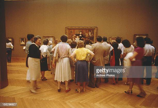 Artlovers gather around PierreAuguste Renoir's painting of Madame Georges Charpentier and her children at the Metropolitan Museum of Art New York...