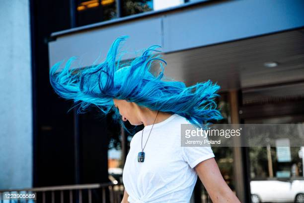 artsy low angle portrait shot of a beautiful, carefree spunky fashionable young woman with fun cute teal blue green dyed hair standing tossing her hair in the wind outdoors in the summer - blue hair stock pictures, royalty-free photos & images