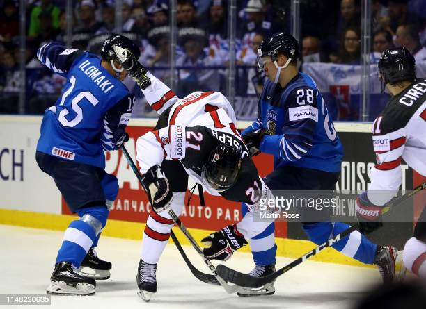 Arttu Ilomaki and Henri Jokiharju of Finland challenges Mathieu Joseph of Canada during the 2019 IIHF Ice Hockey World Championship Slovakia group A...