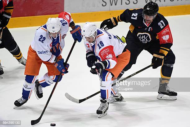 Arttu Ilomäki and VeliMatti Savinainen of Tappara Tampere battle for the puck with Alessandro Chiesa of Lugano during the Champions Hockey League...