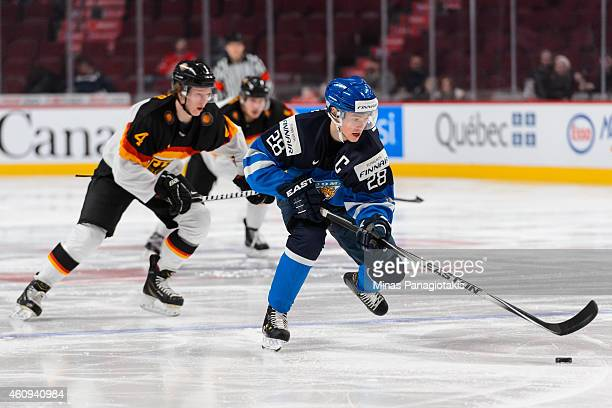 Artturi Lehkonen of Team Finland carries the puck with Jonas Muller of Team Germany following behind in a preliminary round game during the 2015 IIHF...