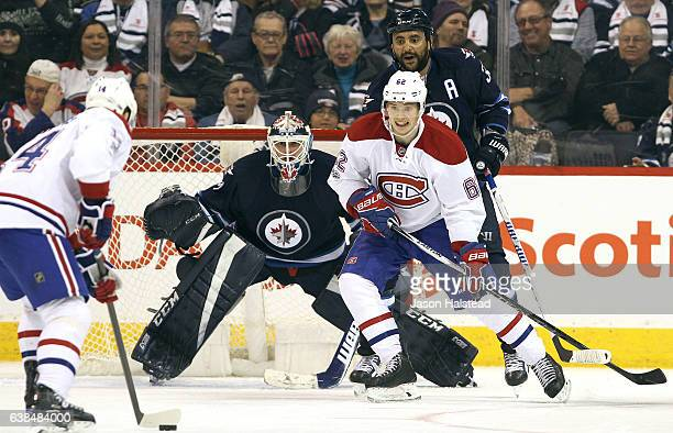 Artturi Lehkonen of the Montreal Canadiens fights for space with Dustin Byfuglien of the Winnipeg Jets in front of Jets goalie Michael Hutchinson...