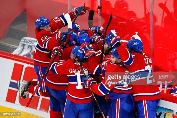 Artturi Lehkonen of the Montreal Canadiens is congratulated by his teammates after scoring the game-winning goal during the first overtime period...