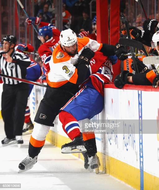 Artturi Lehkonen of the Montreal Canadiens is hit into the boards by Radko Gudas of the Philadelphia Flyers during the first period at the Wells...