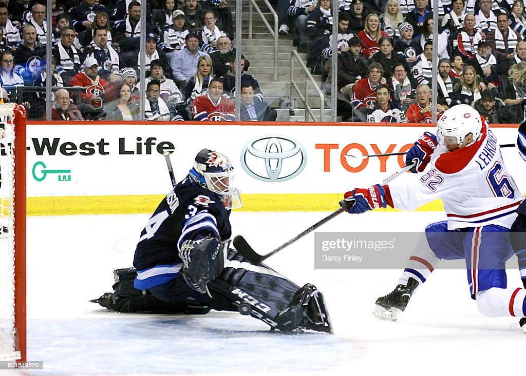 Artturi Lehkonen #62 of the Montreal Canadiens shoots the puck past a sprawling Michael Hutchinson #34 of the Winnipeg Jets for a third period goal at the MTS Centre on January 11, 2017 in Winnipeg, Manitoba, Canada.