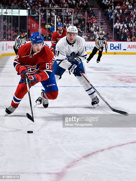 Artturi Lehkonen of the Montreal Canadiens skates the puck against Zach Hyman of the Toronto Maple Leafs during the NHL game at the Bell Centre on...
