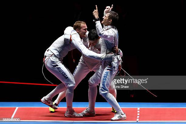 Artur Akhmatkhuzin, Timur Safin and Alexey Cheremisinov of Russia celebrate after winning gold for the Men's Team Foil event on Day 7 of the Rio 2016...