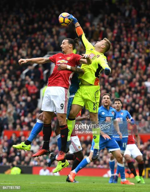 Artur Boruc of AFC Bournemouth attempts to punch the ball away while Zlatan Ibrahimovic of Manchester United attempts to head the ball towards goal...