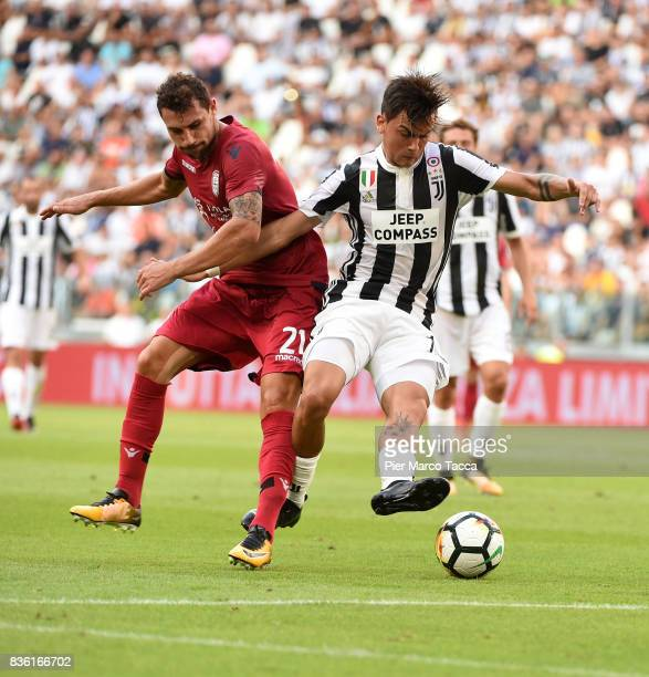 Artur Ionita of Cagliari Calcio competes for the ball with Paulo Dybala of Juventus during the Serie A match between Juventus and Cagliari Calcio at...