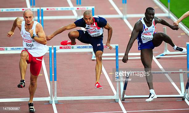 Artur Noga of Poland William Sharman of Great Britain and Ladji Doucoure of France compete in the Men's 100 Metres Hurdles Semi Finals during day...