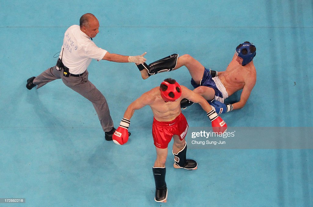 Artur Saurbayev (Blue) of Kazakhstan is knocked down by Aleksei Fedoseev (Red) of Kyrgyzstan in the Kickboxing, Full Contact Men's 63.5kg Round of 16 at Dowon Gymnasium during day five of the 4th Asian Indoor Martial Arts Games on July 3, 2013 in Incheon, South Korea.