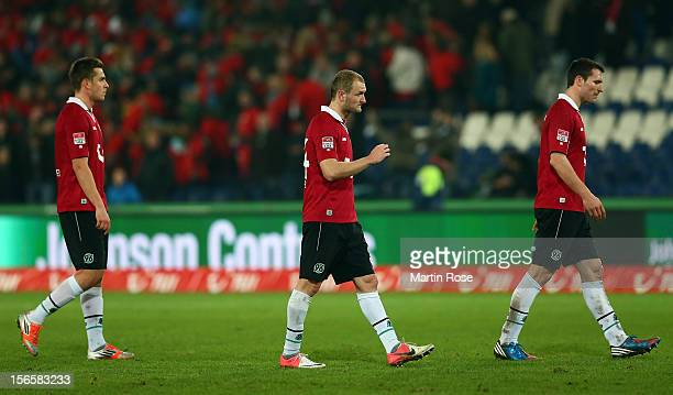 Artur Sobiech, Konstantin Rausch and Mario Eggimann of Hannover walks off dejected after the Bundesliga match between Hannover 96 and SC Freiburg at...