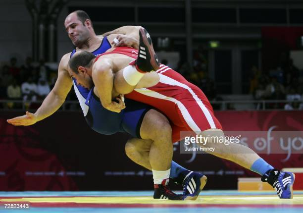 Artur Taymazov of Uzbekistan and Fardin Masoumi Valadi of Iran in action during the Men's Freestyle 120kg medal ceremony at the 15th Asian Games Doha...