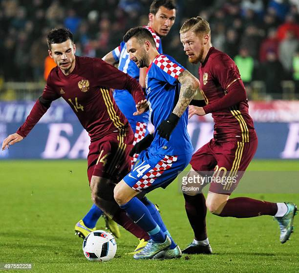 Artur Yusupov and Andrei Semyonov of Russia is challenged by Marcelo Brozovic of Croatia during the international friendly football match between...