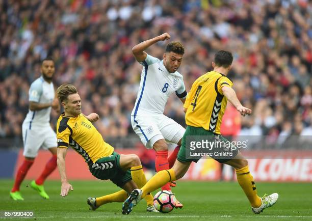 Arturas Zulpa of Lithuania tackles Alex OxladeChamberlaine of England during the FIFA 2018 World Cup Qualifier between England and Lithuania at...