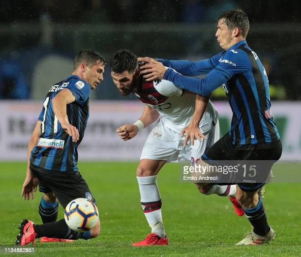 Arturo Calabresi of Bologna FC is challenged by Marten De Roon and Remo Freuler of Atalanta BC during the Serie A match between Atalanta BC and...