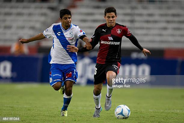 Arturo Gonzalez of Atlas fights for the ball with Luis Robles of Puebla during a 5th round match between Atlas and Puebla as part of the Apertura...
