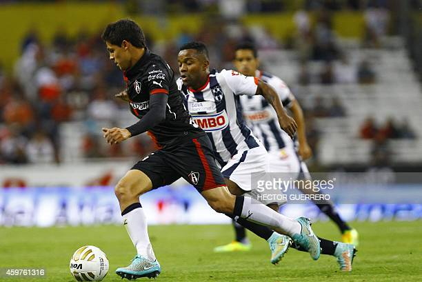 Arturo Gonzalez of Atlas vies for the ball with Dorlan Pavon of Monterrey during a 2014 Mexican Apertura tournament football match in Guadalajara...