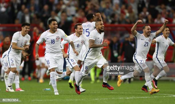 Arturo Vidal and Chile players rush toward Claudio Bravo to celebrate their victory after the penalty shootout during the FIFA Confederations Cup...