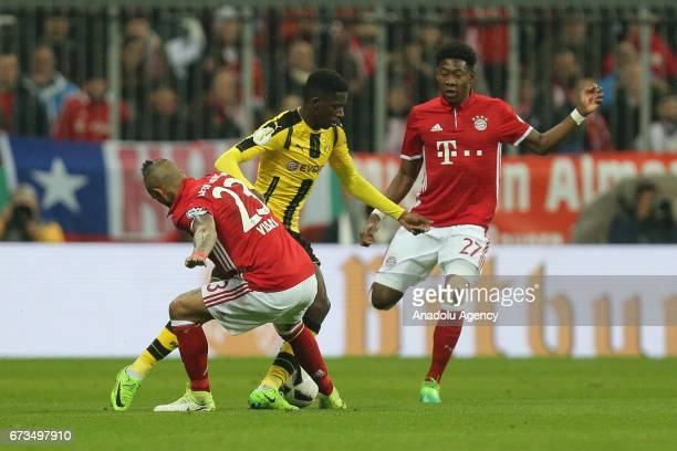 Arturo Vidal and David Alaba of Munich and Ousmane Dembele of Dortmund vie for the ball during the German Cup semi final soccer match between FC...
